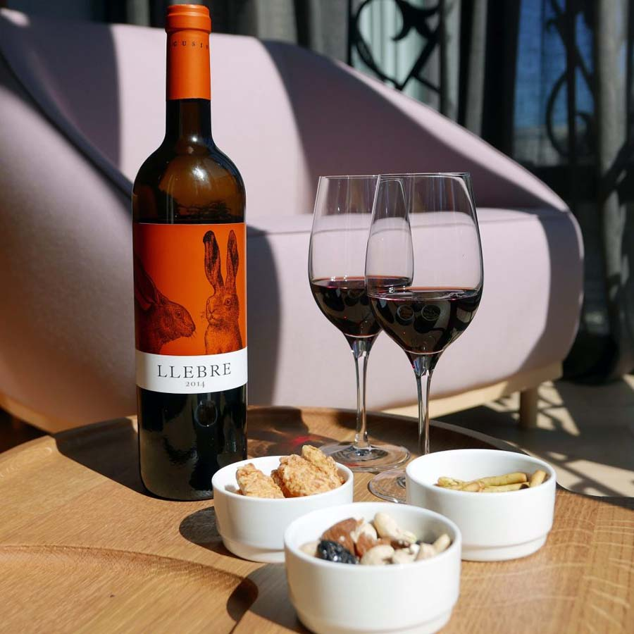 Picture of a bottle of red wine with 2 glasses and bowls of food